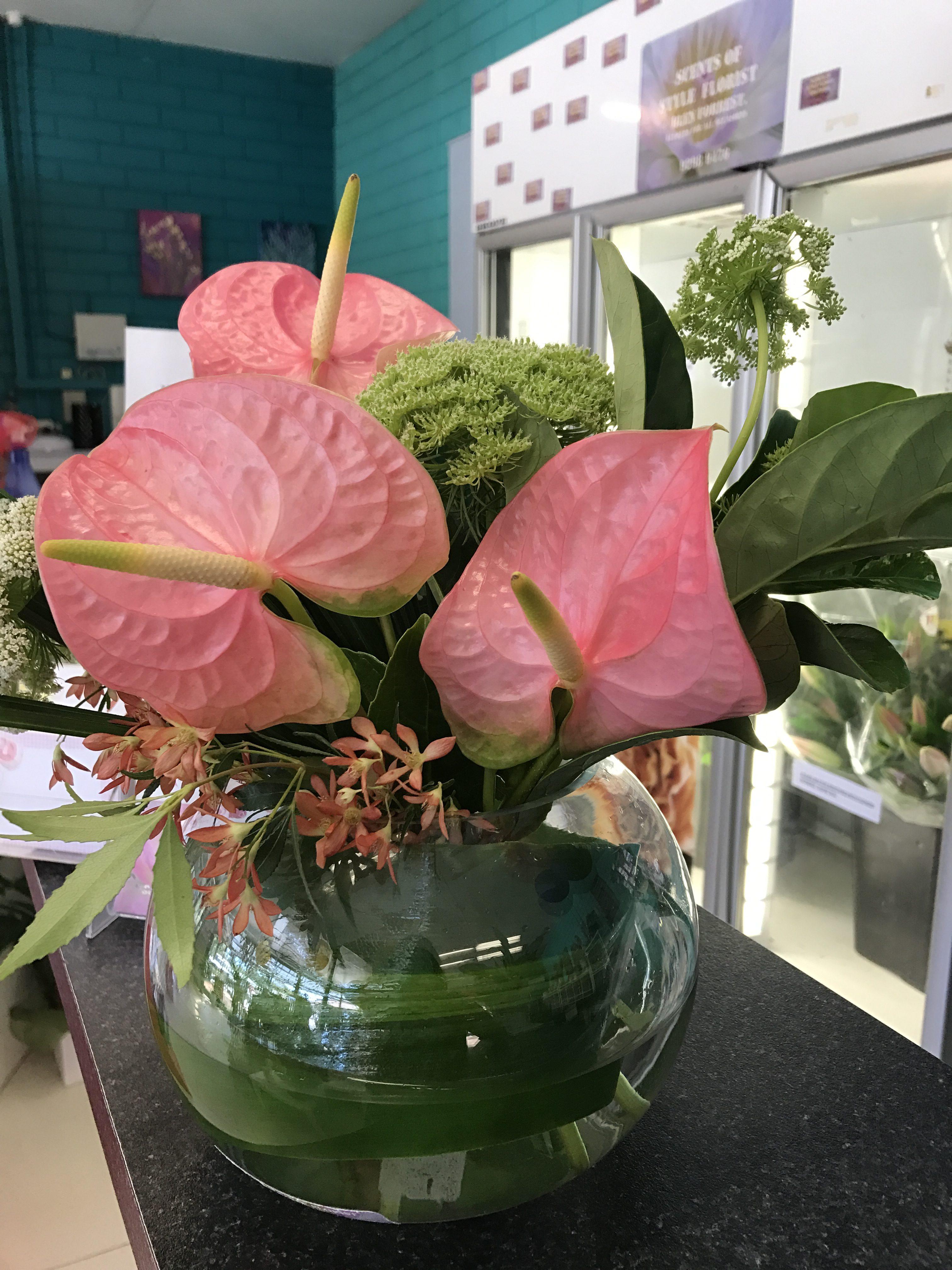Glass fish bowl tropical arrangement
